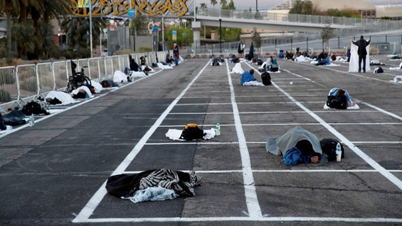 Homeless sleep in a parking lot with painted lines to mark social distance