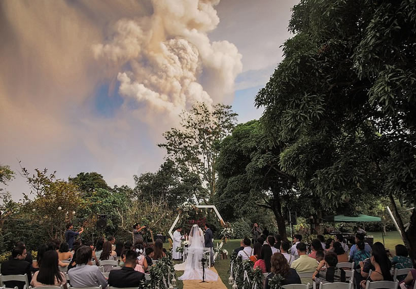 Lava, honour and obey! Couple get married beneath dramatic plume of ash as volcano erupts behind them in the Philippines