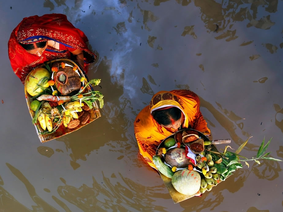 Chhath Puja festival photos: Hindu women wade into rivers and lakes and offer fruit to the sun